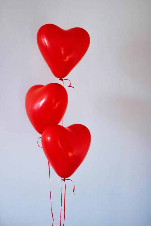 Three heart-shaped helium balloons against a white wall