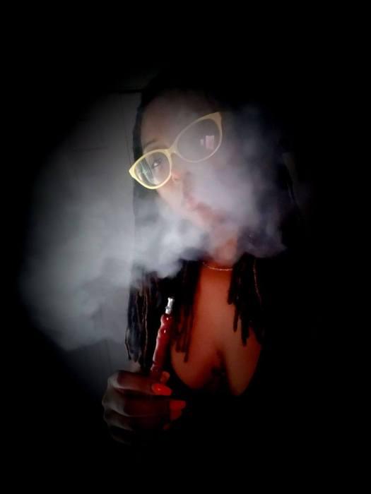 woman in a dark room smoking hookah with smoke around her head