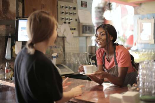 two young women talking across a coffee shop counter