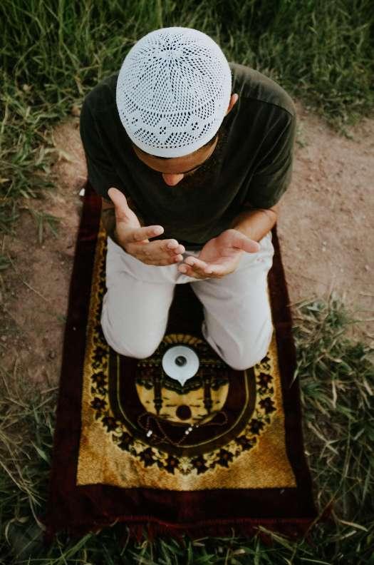Muslim man wearing kufir kneeling on prayer mat on grass