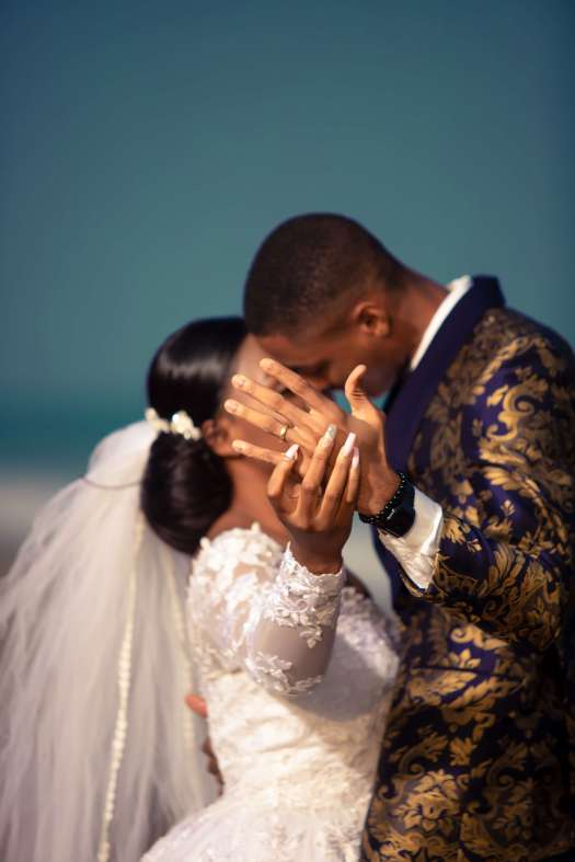 Black bride and groom kiss as bride holds out groom's hand to show his ring