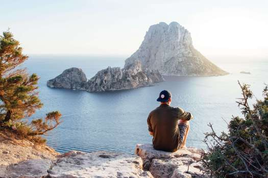 young man sitting at on a mountain overlooking water not dreaming of labor